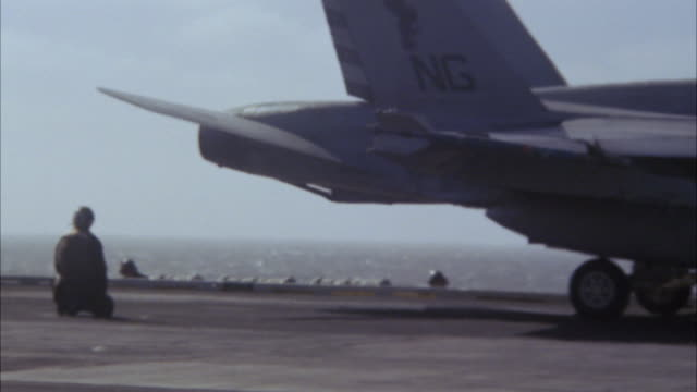 pan left to right of deck of navy aircraft carrier. fa-18 hornet fighter jet and s-3b viking military reconnaissance airplane get towed across frame. fa-18 hornet takes off from catapult. military personnel move and work on deck. ship rises and falls on w - fighter stock videos & royalty-free footage