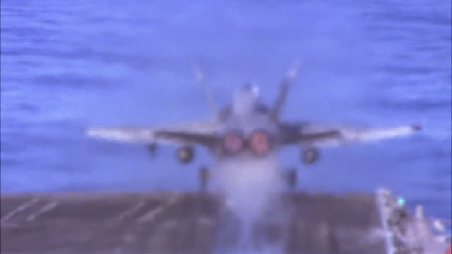 hand held of fa-18 hornet fighter jet taking off from runway of aircraft carrier. military airplane flies above the water. - aircraft carrier stock videos & royalty-free footage