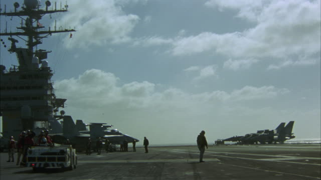 medium angle of aircraft carrier  deck. military personnel wait for another plane to land. - flugzeugträger stock-videos und b-roll-filmmaterial