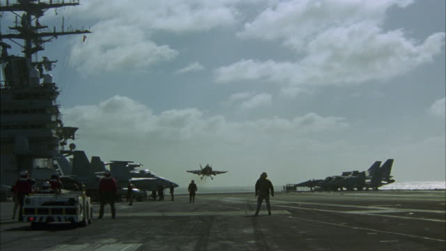 wide angle of fa-18 hornet fighter jet. military airplane lands on aircraft carrier deck. military personnel guide plane into position. - aircraft carrier stock videos & royalty-free footage