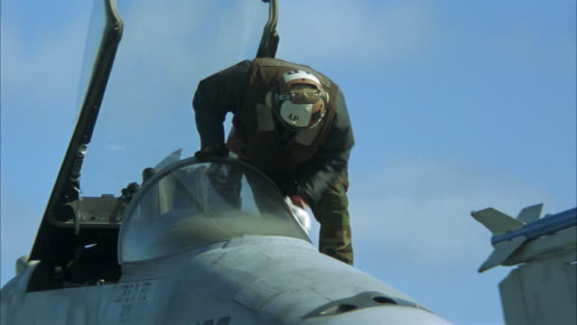 pan left to right of military personal and mechanics working on fighter jets or military airplanes on aircraft carrier deck. one man cleans the windshield, another refuels. fa-18 hornets. - aircraft carrier stock videos & royalty-free footage