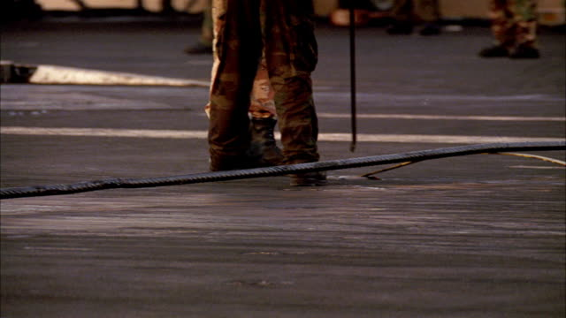 hand held angle of military personnel, seaman, or sailor on aircraft carrier deck. he tightens the brake cable used for jet landings. arresting cable. - sailor stock videos & royalty-free footage