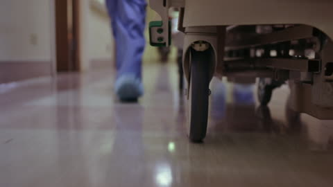 vídeos y material grabado en eventos de stock de close angle of wheel of a hospital bed that is being pushed through the hallway of a hospital. the feet and legs of a nurse or doctor walking quickly next to bed. person is wearing scrubs. could be an emergency. - pasillo característica de edificio