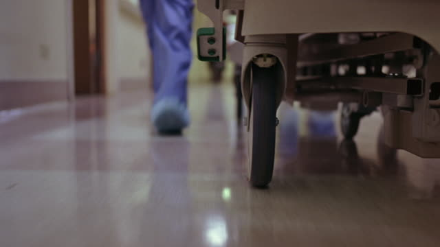 vídeos de stock, filmes e b-roll de close angle of wheel of a hospital bed that is being pushed through the hallway of a hospital. the feet and legs of a nurse or doctor walking quickly next to bed. person is wearing scrubs. could be an emergency. - hospital