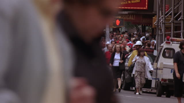 "wide angle of pedestrians, people walking on crowded sidewalk of york city street in times square. cars, taxis driving and people walking past camera in fg. marquee reading ""the drowsy chaperone"" visible on right side of street. intersections. - road junction stock videos & royalty-free footage"