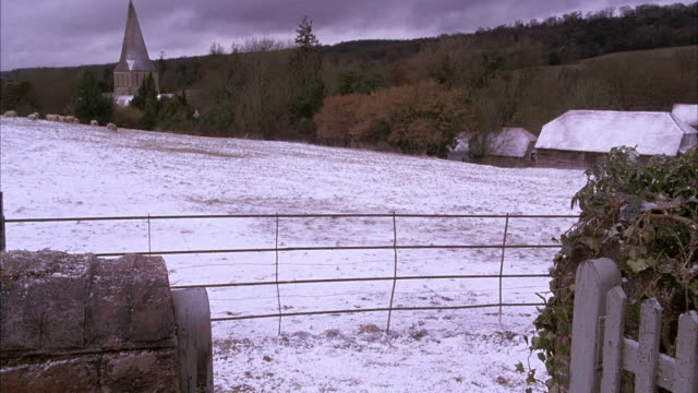 wide angle of stone wall and picket gate. snow covered hillside in bg. shrubs and bushes. church with steeple in bg. english countryside. gate open. sheep on meadow or field in bg. could be farmland. - film stock videos & royalty-free footage