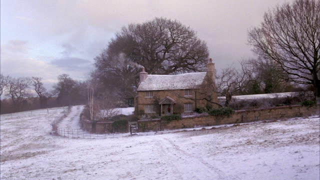 WIDE ANGLE OF ENGLISH FARMHOUSE OR COTTAGE. SNOW COVERS ROOF OF HOUSE AND GROUND. STONE WALL WITH IVY SURROUNDS COTTAGE. BARE WINTER TREES AND SMOKE COMING OUT OF CHIMNEY. RURAL AREA. FIELD IN FG.