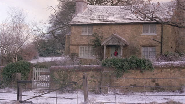 WIDE ANGLE OF ENGLISH FARMHOUSE OR COTTAGE. SNOW COVERS ROOF OF HOUSE AND GROUND. STONE WALL WITH IVY SURROUNDS COTTAGE. PICKET GATE. BARE WINTER TREES AND SMOKE COMING OUT OF CHIMNEY. RURAL AREA. FIELD IN FG.