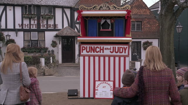 """wide angle of puppet show street performance. women and children stand watching puppet show booth with """"punch and judy"""" painted on front. puppet appears in booth. tudor style buiding in bg with sign reading """"the whitehorse."""" could be tavern or pub. perfor - puppet stock videos & royalty-free footage"""