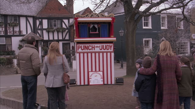 "wide angle of puppet show street performance. women and children stand watching puppet show booth with ""punch and judy"" painted on front. puppet appears in booth. tudor style buiding in bg with sign reading ""the whitehorse."" could be tavern or pub. perfor - puppentheater figur stock-videos und b-roll-filmmaterial"
