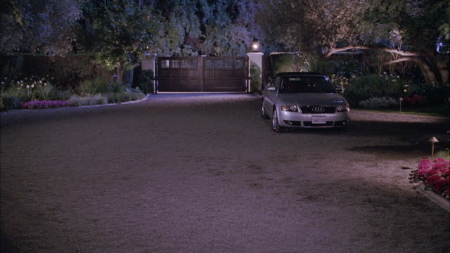 WIDE ANGLE OF SILVER AUDI SEDAN PARKED IN DRIVEWAY. CAR IS PARKED ON SPACIOUS DRIVEWAY WITH GATE AND WALL IN BG. TREES AND FLOWERS IN GARDEN SURROUNDING DRIVEWAY.