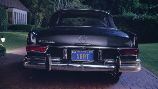 WIDE ANGLE OF BLACK MERCEDES CAR PARKED ON BRICK DRIVEWAY. TREES, A LAWN, AND PART OF A HOUSE CAN BE SEEN IN BACKGROUND. CAR HAS A CALIFORNIA LICENSE PLATE.