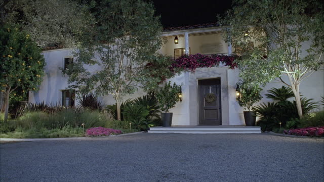 stockvideo's en b-roll-footage met wide angle of two story spanish style house or mansion. upper class house has second story balcony. trees and plants blowing in wind. gravel driveway leads to front door with wreath. could be christmas time. could be bel air, brentwood or beverly hills. - landhuis