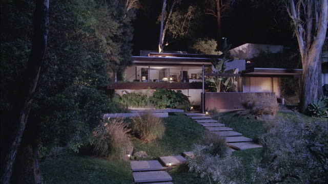 wide angle ofmodern upper class house and front yard. yard has path of stone steps, bushes, plants, and trees. wind blows through trees and bushes. - oberschicht stock-videos und b-roll-filmmaterial