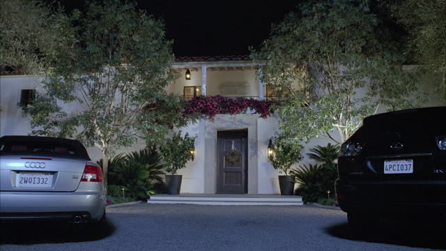 WIDE ANGLE OF TWO STORY SPANISH STYLE HOUSE OR MANSION. UPPER CLASS HOUSE HAS SECOND STORY BALCONY. TREES AND PLANTS BLOWING IN WIND. GRAVEL DRIVEWAY LEADS TO FRONT DOOR WITH WREATH. COULD BE CHRISTMAS TIME. COULD BE BEL AIR, BRENTWOOD OR BEVERLY HILLS. A