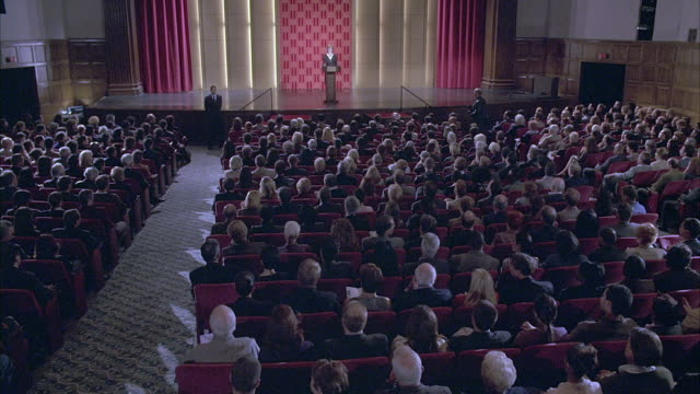 wide angle of audience watching woman at podium in director's guild theater. men in women in seats begin to clap, stand and turn away from stage, giving unseen person standing ovation. camera flashbulb flashes. could be awards ceremony. - human stage点の映像素材/bロール