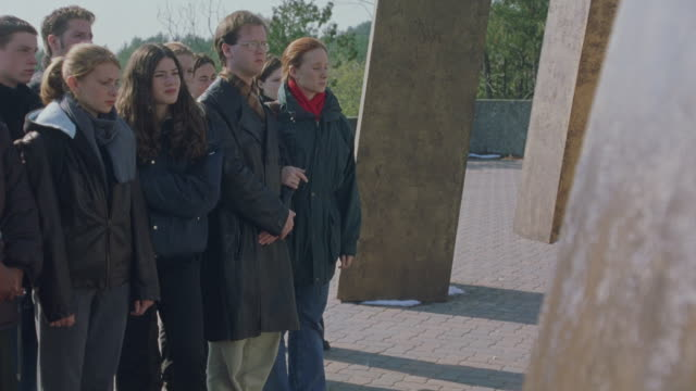 medium angle of a group of students on a university or college campus.  they stand together next to a large sculpture or art installation staring at something off screen. - ontario canada stock videos & royalty-free footage