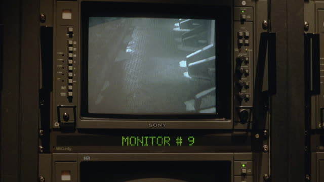 """pan left to right from """"monitor 9"""" showing security camera view of exterior walk way to """"monitor 12"""" showing different view and back. burn in. surveillance. - telecamera di sorveglianza video stock e b–roll"""