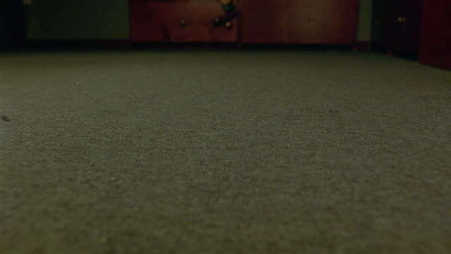 close angle of carpeted floor as boom microphone falls to ground, bounces on carpet. unseen person picks up recording device. could also be on movie set. series. - カーペット点の映像素材/bロール