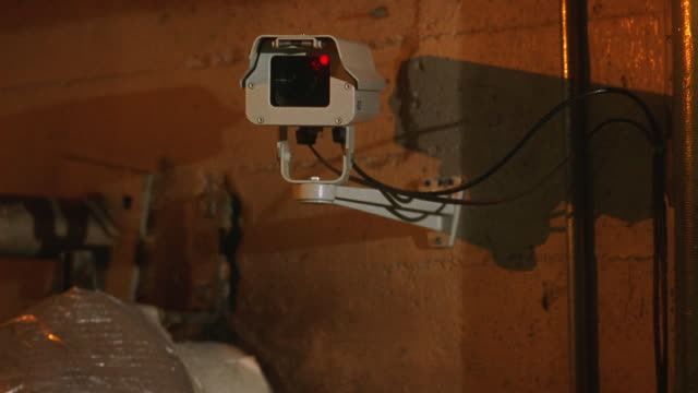 vidéos et rushes de wide angle of surveillance camera mounted on wall of cement block building. lights flash, recording light blinks. security camera could be on warehouse, garage. could be break in. - sécurité
