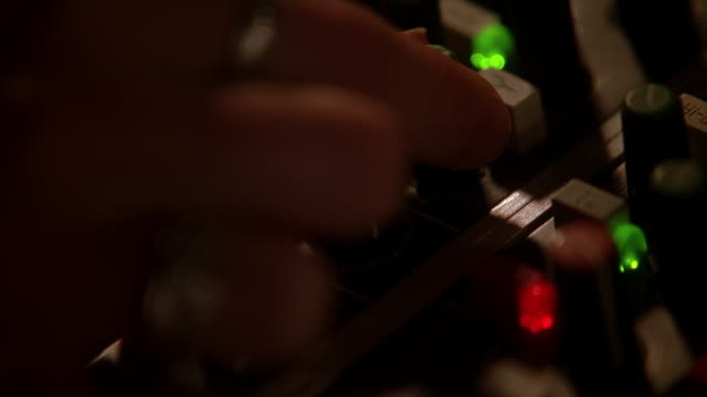 vídeos y material grabado en eventos de stock de close angle of buttons and levers on sound board in recording studio or sound stage. woman's hand pushes buttons, turns knobs. music. recording devices. - tiempo real grabación