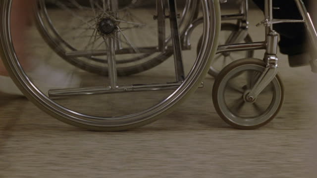 tracking shot shows wheels of wheelchair being pushed through hospital or nursing home with nurse's and patient's feet visible. - wheelchair stock videos & royalty-free footage