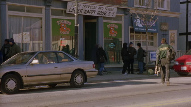 """WIDE ANGLE OF EXTERIOR STOREFRONT OF BAR, PUB OR TAVERN WITH SIGN READING """"TIGERS DEN"""" AND BANNER ADVERTISING """"LADIES HAPPY HOUR 5-7."""" COLLEGE STUDENT, MAN IN """"TIGERS"""" LETTERMAN'S JACKET WALKS ACROSS STREET TOWARDS BAR TO MEET PEOPLE STANDING IN FRONT. MA"""