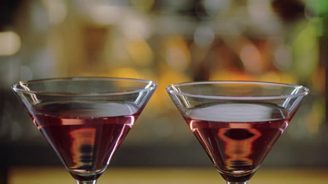 stockvideo's en b-roll-footage met close angle of cocktails, martini glasses filled with alcohol on top of bar as gloved hand pours powder into glasses, could be date rape drug or poison. waitress, waiter picks up glasses on tray. liquor. beverages. crimes. - martiniglas