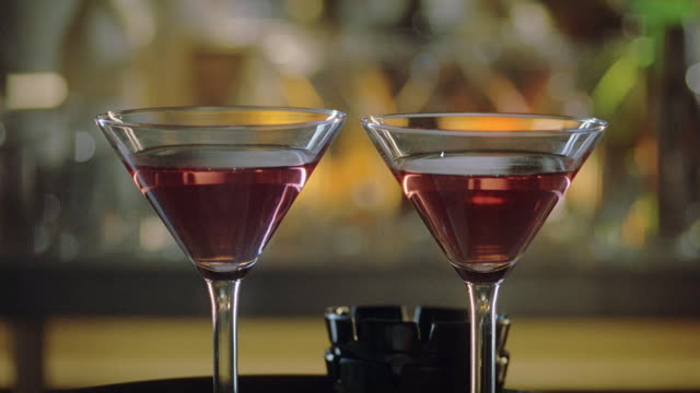 stockvideo's en b-roll-footage met close angle of cocktails, martini glasses filled with alcohol on top of bar as gloved hand pours powder into glasses. could be date rape drug or poison. liquor. beverages. crimes. - martiniglas