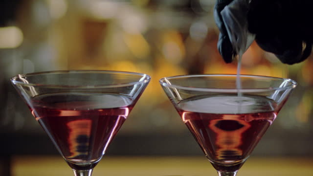 stockvideo's en b-roll-footage met close angle of cocktails, martini glasses filled with alcohol on top of bar as gloved hand pours powder into glasses, could be date rape drug or poison. liquor. beverages. crimes. - martiniglas