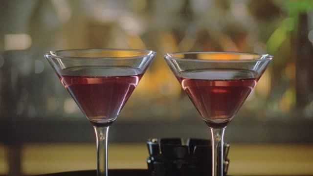 stockvideo's en b-roll-footage met close angle of cocktails, martini glasses filled with alcohol on top of bar with ashtray in background.  liquor. beverages. - martiniglas