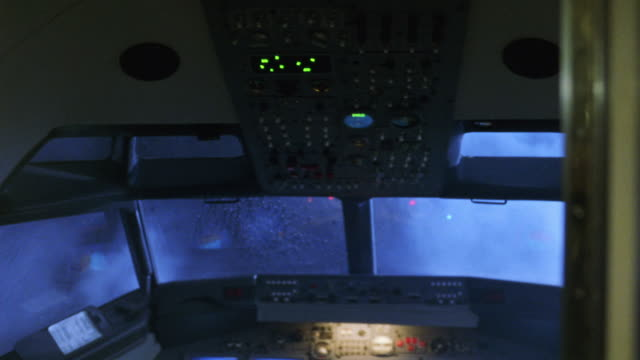 vídeos y material grabado en eventos de stock de hand held pans around cockpit in commercial airliner showing corpses of pilot and copilot slumped in seats with blood on neck and chests. instrument panels blink, lightning flashes as plane bumps up and down. could be used for storm, crash, terrorist atta - cabina de mando