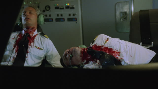 medium angle of corpses of pilot and copilot slumped in airplane cockpit seats with blood on neck and chests. lightning flashes as plane bumps up and down. could be used for storm, crash, terrorist attack. gore. - pilot bildbanksvideor och videomaterial från bakom kulisserna