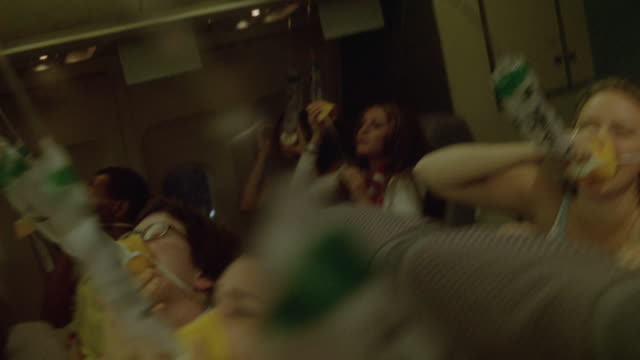 hand held moves through cabin of commercial airliner, airplane showing panicked passengers applying deployed oxygen masks to faces as light, lightning flashes. people wear hawaiian shirts, leis. could be used for crash landing, emergency. - syrgasmask bildbanksvideor och videomaterial från bakom kulisserna