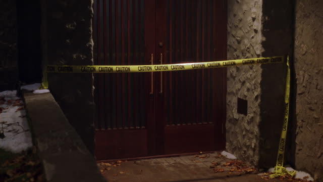 """stockvideo's en b-roll-footage met medium angle of doorway with """"caution"""" tape blocking entry. double doors are part of concrete building, could be museum, university or college building. police tape. - afzetlint"""