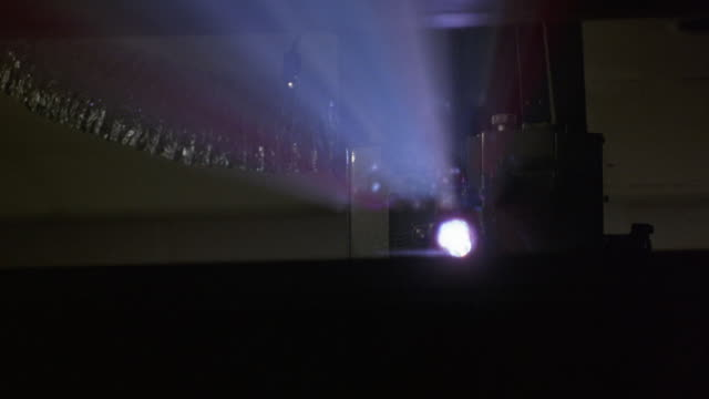 medium angle of light coming through a projector in a cinema or movie theater.  light shoots through dust in the air, causing different colors of light to flash in the theatre. - projection equipment stock videos & royalty-free footage