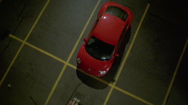 high angle down of red 2000 volkswagen beetle car parked in empty parking lot. zoom in on car reveals rain on windshield and roof. - 1998 stock videos and b-roll footage
