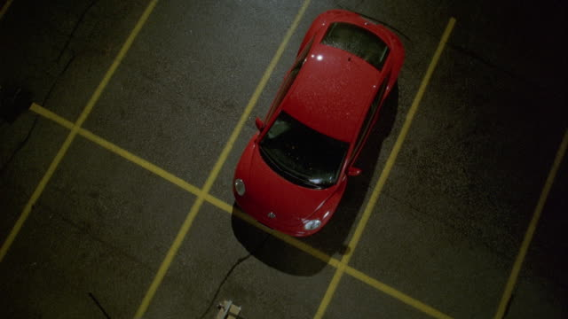 high angle down of red 2000 volkswagen beetle car parked in empty parking lot. zoom in on car reveals rain on windshield and roof. - volkswagen stock-videos und b-roll-filmmaterial