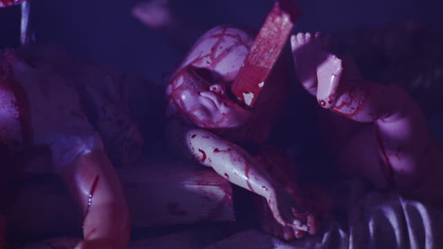 close angle of mound of mutilated baby dolls or mannequins covered in fake blood and pierced with long nails or spears. flashing lights or lightning. could be nightmare. - ドール点の映像素材/bロール