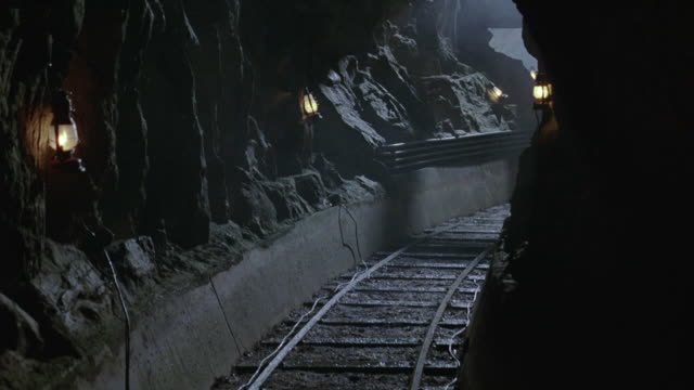 steadicam moving through underground mine tunnel along mining cars track. lanterns hanging on rugged rock walls. - bergbau stock-videos und b-roll-filmmaterial