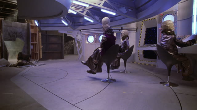wide angle of movie set of three aliens in swivel chairs at control panel of command deck of spaceship in outerspace. could be exhibit. - außerirdischer stock-videos und b-roll-filmmaterial