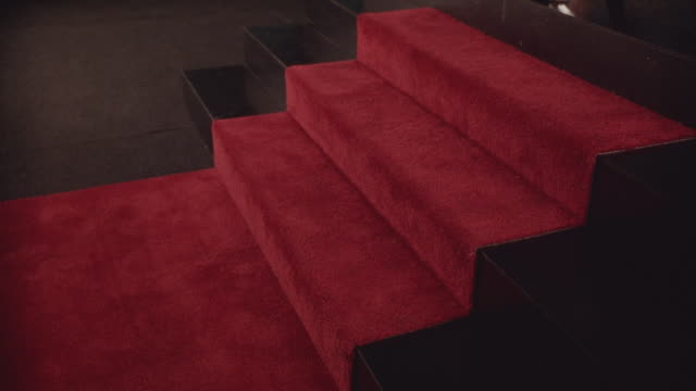 vídeos y material grabado en eventos de stock de close angle of red carpet along sidewalk and stairs. award falls down stairs and breaks apart. could be awards show. - alfombra roja