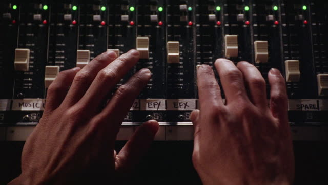 close angle of hands on dials of mixing board or  sound board. green and red glowing lights. - recording studio stock videos & royalty-free footage
