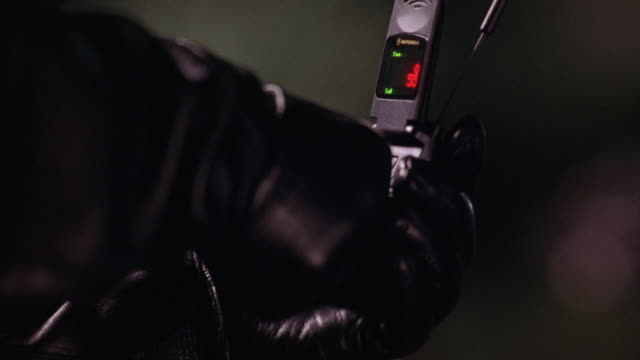 """close angle of motorola flip style cell phone with antenna in gloved hand of person wearing black leather. red numbers, green lights and """"no srvc"""" message on display screen of phone. - 2000s style点の映像素材/bロール"""