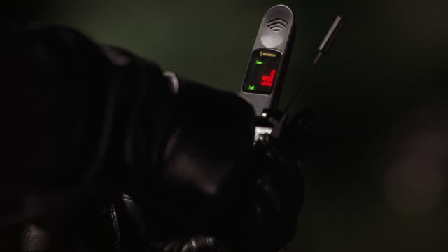 """CLOSE ANGLE OF MOTOROLA FLIP STYLE CELL PHONE WITH ANTENNA IN GLOVED HAND OF PERSON WEARING BLACK LEATHER. RED NUMBERS, GREEN LIGHTS AND """"NO SRVC"""" MESSAGE ON DISPLAY SCREEN."""