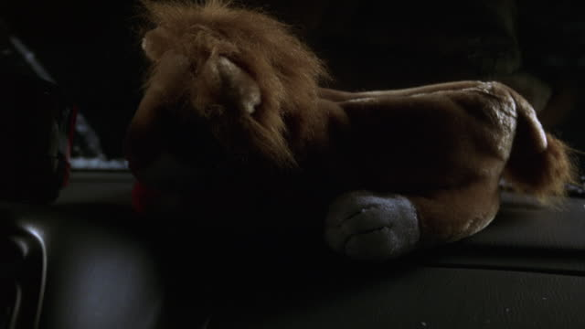 close angle of stuffed animal lion or toy on dashboard of car. windshield wipers brush away falling snow from window. headlights from passing cars illuminate car interior. driving. - ぬいぐるみ点の映像素材/bロール