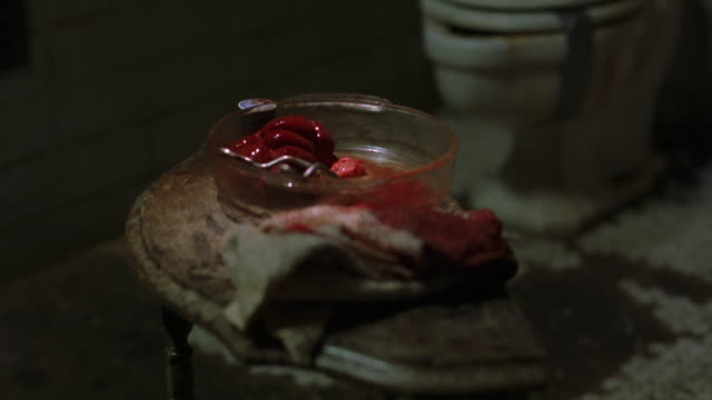 MEDIUM ANGLE OF HUMAN INTERNAL ORGAN, POSSIBLY KIDNEY, IN GLASS DISH WITH SURGICAL TOOL SCISSORS AND BLOODY TOWEL ON OLD TABLE. DIRTY OLD TOILET IN BG. SURGERIES. GORE.