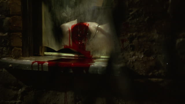 medium angle of window with broken glass transformed into makeshift guillotine. headless mannequin or dummy bleeds onto window sill. man in black leather jacket and latex gloves raises window and tosses out bloody internal organ. possible kidney. gore. ex - execution by guillotine stock videos & royalty-free footage