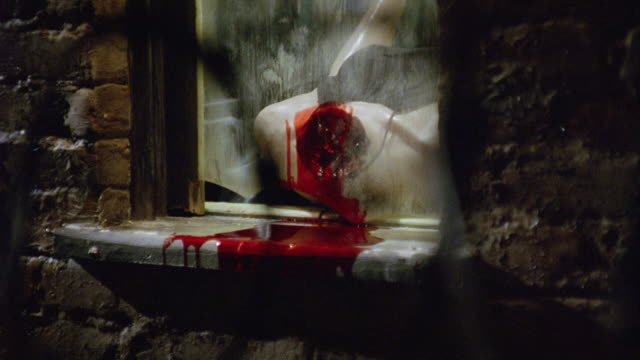 medium angle of window with broken glass transformed into makeshift guillotine. headless mannequin or dummy bleeds onto window sill. man in black leather jacket and latex gloves raises window and tosses out bloody internal organ. window slams and organ re - execution by guillotine stock videos & royalty-free footage