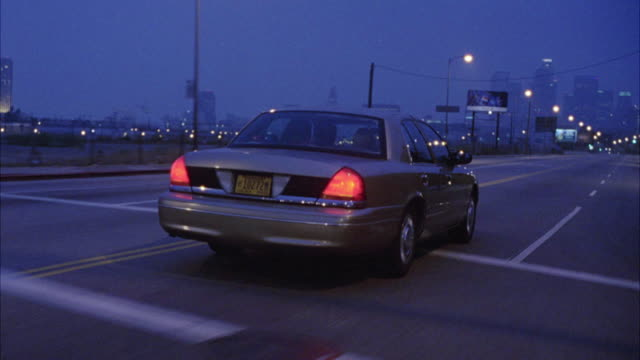 TRACKING SHOT BUMPERCAM OF 1999 FORD CROWN VICTORIA SEDAN CAR WITH HEADLIGHTS DRIVING ON CITY STREET WITH STREET LAMPS. COULD BE UNMARKED POLICE CAR. YELLOW OREGON LICENSE PLATE. LOS ANGELES SKYLINE IN BG.